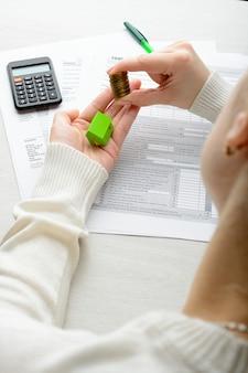 In zijn handen een stapel munten en papier over het huis over belastingaangifte calculator
