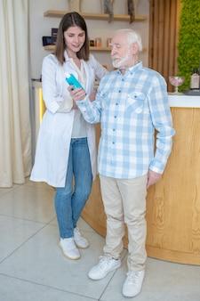 Ina schoonheidssalon. winkelbediende die een oude man helpt bij het kiezen van de lichaamsverzorgingsproducten
