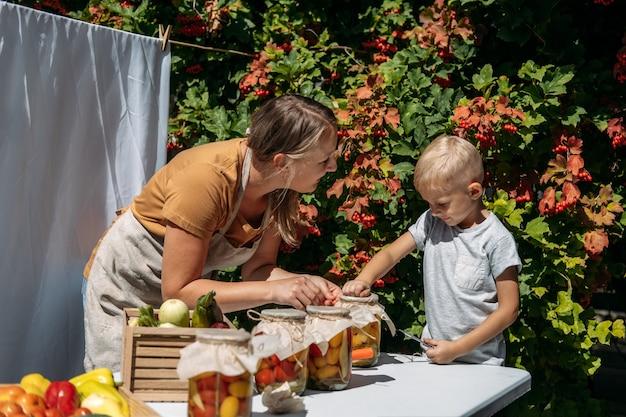 Inblikken van tuingroenten conservering van tomaten paprika's courgette groenten moeder en zoon uit blik