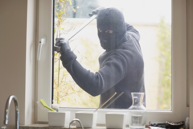 Inbreker die een keukenvenster breekt