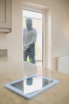 Inbreker die tabletpc door keukendeur bekijkt