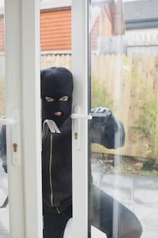Inbreker die voorzichtig de deur opent