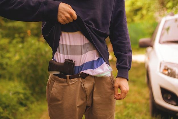 Inbreker in masker die het pistool buiten vasthoudt en herlaadt