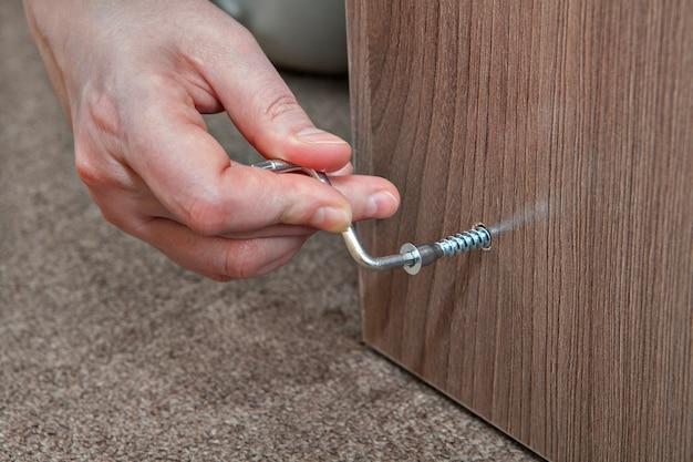 Inbussleutel, inbussleutel van menselijke hand die thuis meubels monteert.