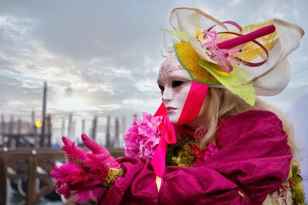 Incognitovrouw in sierlijk carnavalskostuum met gezichtsmasker en hoed poseert op het san marco-plein