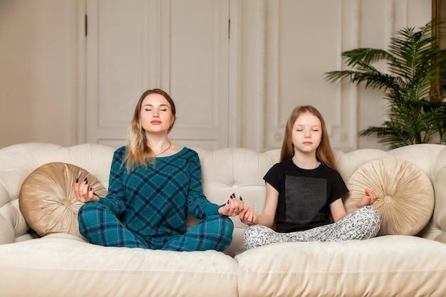 Indachtig gelukkige moeder met schattige grappige kind dochter doet yoga oefening thuis in de woonkamer, moeder en meisje zitten in lotus houding samen op de bank, moeder leert kind te mediteren. ruimte kopiëren