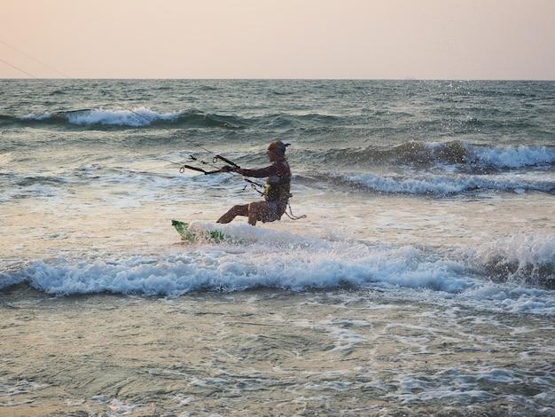 India, goa, arambol, een man die dichtbij de kust bij zonsondergang kitesurft