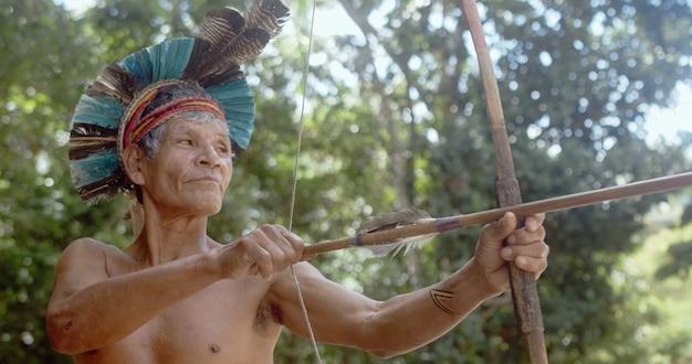 Indiaan van de patax stam met veren hoofdtooi en pijl en boog