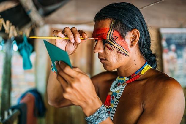 Indiaan van de pataxã³-stam, gebruikt een spiegel en doet schminken