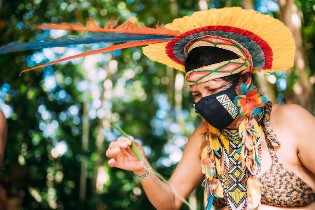 Indiaan van de pataxã³-stam met een hoofdtooi van veren en een beschermend masker tegen de covid-19 pandemie