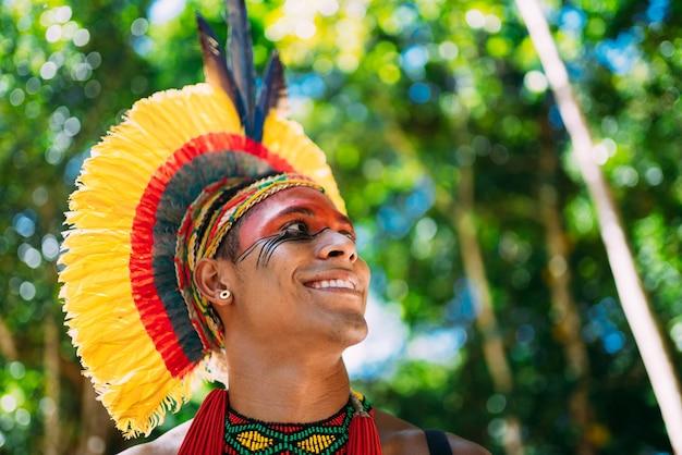 Indiaan van de pataxã³ stam met naar rechts kijkende veren hoofdtooi. inheems uit brazilië met traditionele gezichtsschilderijen