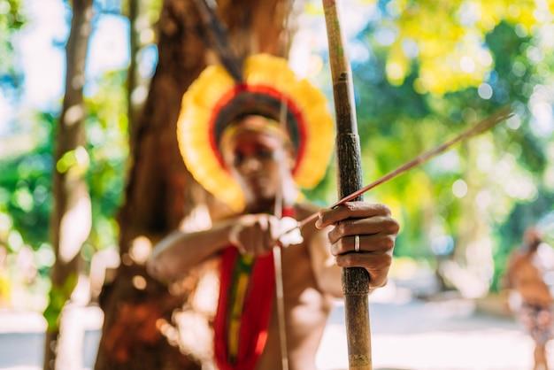 Indiaan van de pataxã³ stam met pijl en boog. braziliaanse indiaan met veren hoofdtooi en ketting