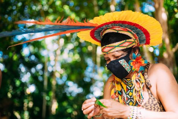 Indiaan van de pataxã³ stam met veren hoofdtooi en beschermend masker