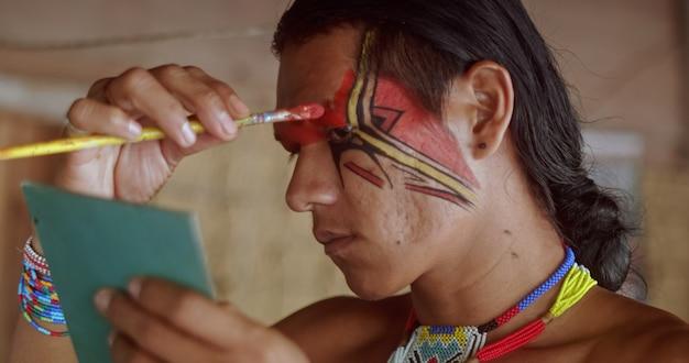 Indiaan van de pataxo-stam met behulp van een spiegel en schminken