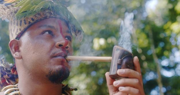 Indiaanse opperhoofd van de pataxã³-stam rookpijp. braziliaanse indiaan met veren hoofdtooi en ketting