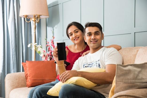Indiaas aziatisch jong stel dat samen smartphone gebruikt terwijl ze op de bank of bank zitten en een moderne binnenruimte of thuis