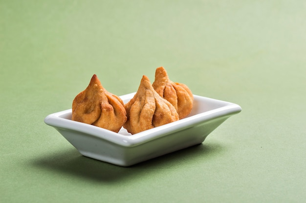 Indiaas eten: modak op groene ruimte, maharashtra sweet dish, favoriet snoepje van lord ganesha, wenskaartontwerp. kopie-ruimte.