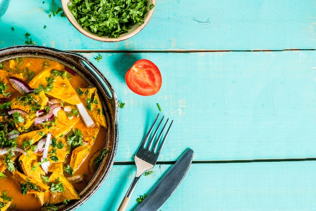 Indiaas eten recepten, indiase omelet masala ei curry, met verse groententomaat, hete chilipeper, peterselie, lichtblauwe houten, bovenaanzicht
