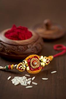 Indiaas festival: raksha bandhan met een elegante rakhi, rijstkorrels en kumkum. een traditionele indiase polsband die een symbool is van liefde tussen broers en zussen.