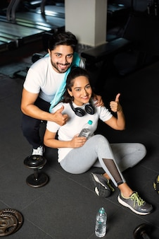 Indiaas jong stel in de sportschool die rust of een pauze neemt van het sporten, water drinkt, positieve uitdrukkingen toont