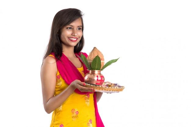 Indiaas meisje met een traditionele koperen kalash met pooja thali, indian festival, koperen kalash met kokos en mangoblad met bloemendecoratie, essentieel in hindu pooja.