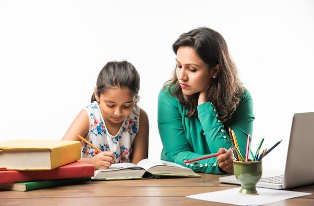 Indiaas meisje studeert met moeder of leraar aan studeertafel met laptopcomputer, boeken en heeft plezier bij het leren