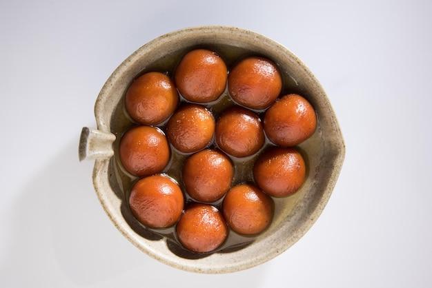 Indiaas zoet eten gulab jamun geserveerd in een ronde keramische kom