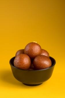 Indian dessert of sweet dish: gulab jamun in kom op gele achtergrond.