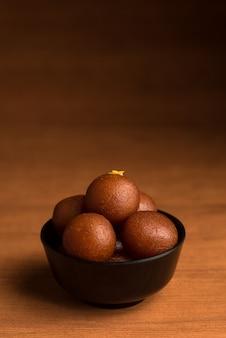 Indian dessert of sweet dish: gulab jamun in kom op houten achtergrond.