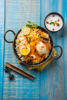 Indian egg biryani of anda rijst geserveerd in kadhai of kadai met yoghurtdip, selectieve focus