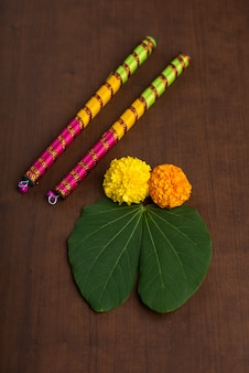 Indian festival dussehra en navratri, met gouden blad- en goudsbloembloemen met dandiya-sticks.