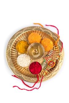 Indian festival: rakhi met rijstkorrels, kumkum, snoep en diya op bord met een elegante rakhi. een traditionele indiase polsband die een symbool is van liefde tussen broers en zussen