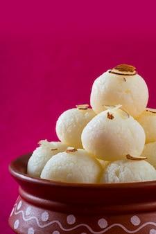 Indian sweet of dessert - rasgulla, famous bengali sweet in clay bowl op een roze achtergrond.