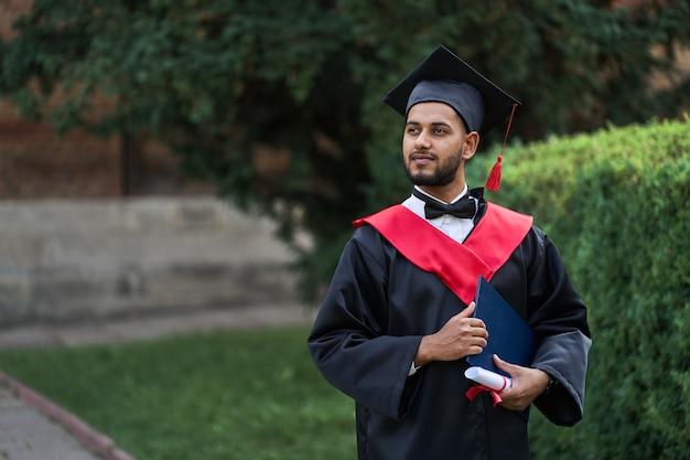 Indiase afgestudeerde in afstudeergewaad met diploma in kopieerruimte van de universiteitscampus.