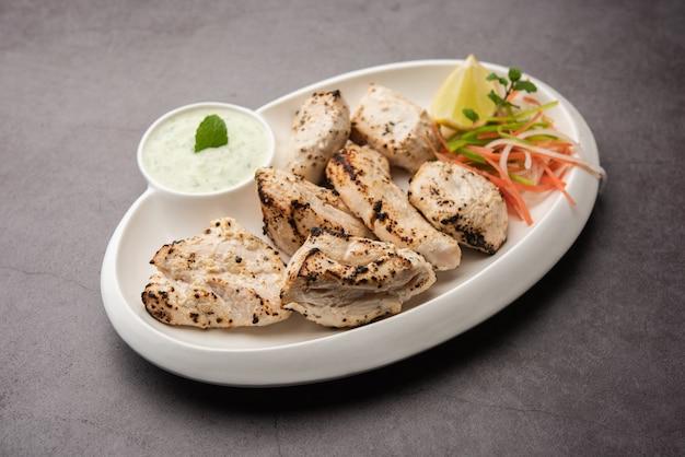 Indiase afghaanse kip malai tikka is een gegrilde murgh romige kabab geserveerd met frisse salade