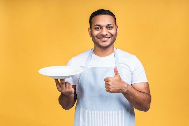 Indiase afro-amerikaanse chef-kok of bakker man in gestreepte schort geïsoleerd op gele achtergrond. koken voedsel concept. bespotten kopie ruimte. houd een lege lege plaat vast met plaats voor eten.