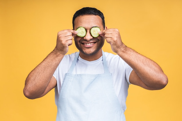 Indiase afro-amerikaanse jongeman die plakjes komkommer over de ogen houdt en glimlacht of lacht. geïsoleerd op gele achtergrond. kook voedsel bereiden.
