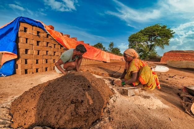 Indiase arbeiders maken met de hand bakstenen van klei in de fabriek of op het veld.