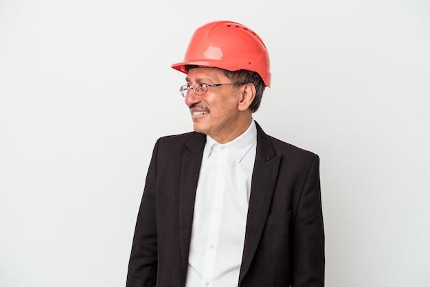 Indiase architect man van middelbare leeftijd geïsoleerd op een witte achtergrond kijkt opzij glimlachend, vrolijk en aangenaam.