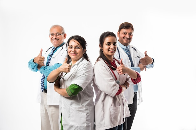 Indiase aziatische artsen groepsfoto met succes of duimen omhoog teken. staande geïsoleerd op een witte achtergrond. selectieve focus