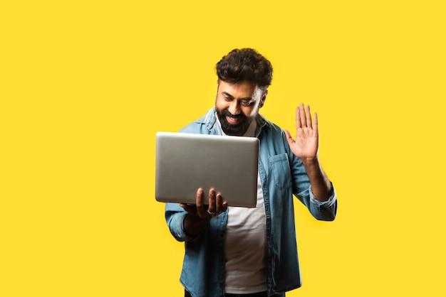 Indiase aziatische bebaarde jongeman in casual kleding met laptop terwijl hij op geel staat