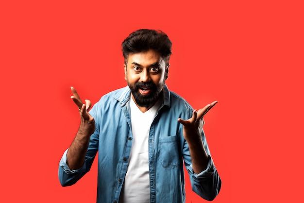 Indiase aziatische bebaarde man met verbaasde of wauw-looks, staande op rood