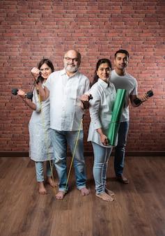 Indiase aziatische familie die thuis traint. senior ouders met jonge kinderen die yoga doen, gewicht heffen, theraband gebruiken in het interieur van de woonkamer. indoor trainingsconcept