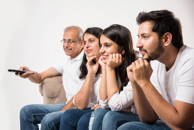 Indiase aziatische familie van meerdere generaties die thuis tv kijkt terwijl ze op de bank of bank zitten, zijaanzicht, selectieve focus