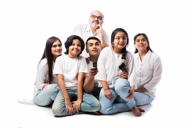 Indiase aziatische familie van meerdere generaties van zes die thuis samen tv kijken en plezier hebben, zittend op de vloer tegen een witte achtergrond