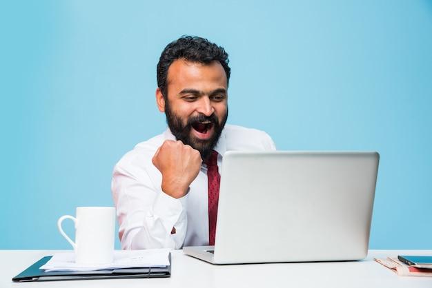 Indiase aziatische jonge bebaarde zakenman met gestrekte handen poseren tijdens het werken op laptop, computer vieren victory