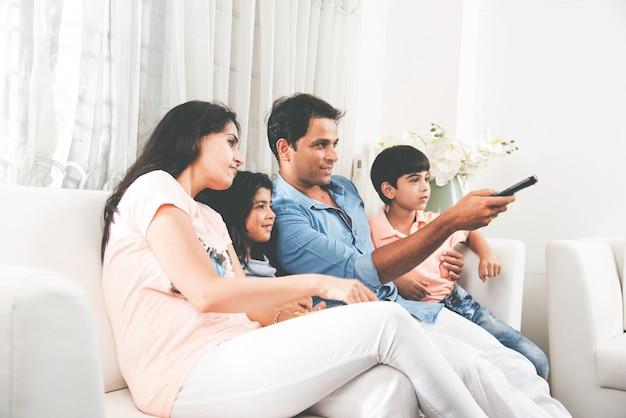 Indiase aziatische jonge familie samen tv kijken terwijl ze op de bank zitten, selectieve focus