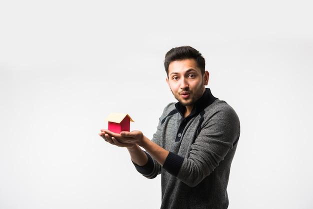 Indiase aziatische jonge man met huis of onroerend goed model, staande geïsoleerd op witte achtergrond