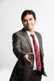 Indiase aziatische jonge zakenman die of nadert voor handdruk, geïsoleerd op witte achtergrond