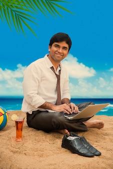 Indiase aziatische jonge zakenman die ontspant of werkt vanaf het strand en geniet van een pauze van het werk